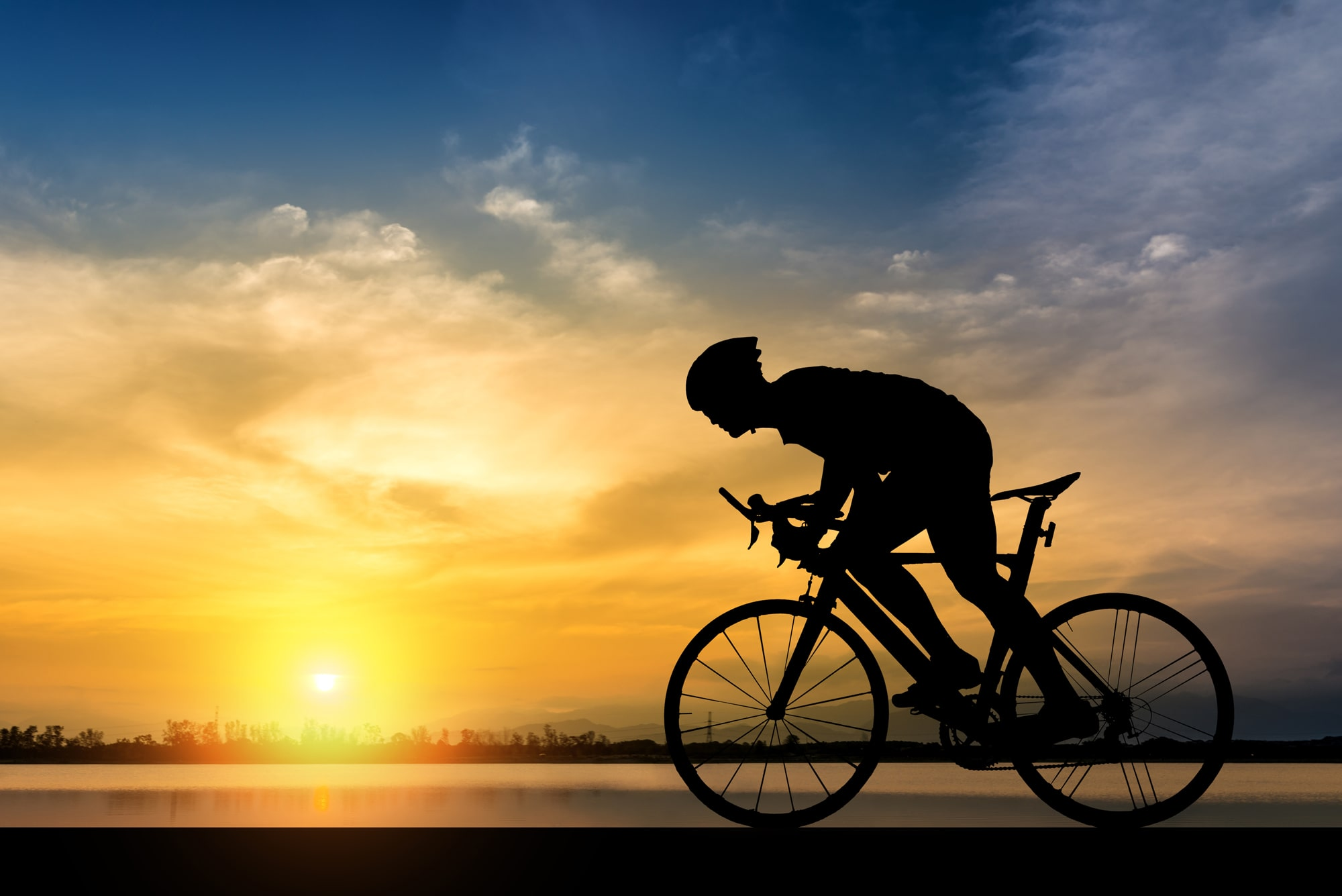 bicycle rider in front of a sunrise
